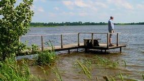 El hombre se coloca en el embarcadero en el lago en tiempo ventoso almacen de video