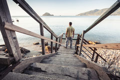 El hombre se coloca en la escalera de madera vieja, costa de mar Fotografía de archivo