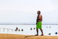 El hombre se coloca en la orilla del mar muerto Foto de archivo libre de regalías