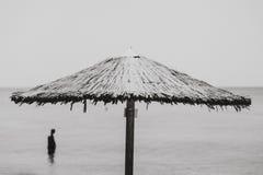 El hombre se coloca en el mar más allá del unbrella imagenes de archivo