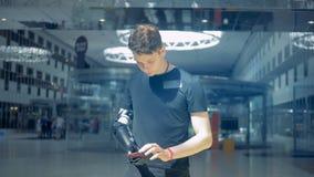El hombre se coloca en un cuarto, mecanografiando en su teléfono con una mano biónica Concepto futurista
