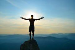El hombre se coloca encima de una montaña con las manos abiertas Imagen de archivo libre de regalías