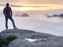 El hombre se coloca solamente en el pico de la roca Caminante que mira al otoño Sun en el horizonte Imagenes de archivo