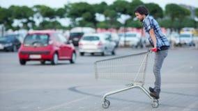 El hombre se divierte en la alameda de compras del estacionamiento Paseos divertidos felices del individuo en el carro de la comp almacen de metraje de vídeo