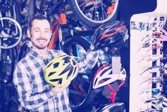 El hombre se elige casco cómodo para conducir la bicicleta Imagen de archivo