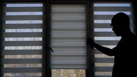 El hombre se está acercando a las ventanas dentro de un hogar contra luz y que cae el blanco las persianas, paisaje del día del o metrajes