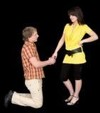 El hombre se está arrodillando a la mujer joven Fotografía de archivo