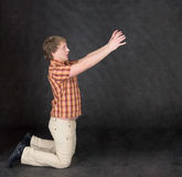 El hombre se está arrodillando y las manos del estiramiento algo Fotos de archivo