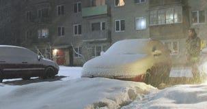 El hombre se está colocando al lado de un coche que ha sido llevado por la nieve almacen de video
