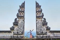 El hombre se está colocando en la puerta del templo de Lempuyang en el isalnd de Bali, fotografía de archivo libre de regalías