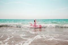 El hombre se está divirtiendo en el flotador inflable de la piscina del flamenco del rosa fotos de archivo