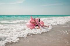El hombre se está divirtiendo en el flotador inflable de la piscina del flamenco del rosa fotos de archivo libres de regalías