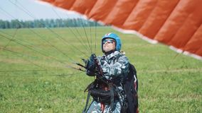 El hombre se está preparando para volar en un ala flexible Person Before Flying On Paraglider en Sunny Day Antes del Paragliding  metrajes