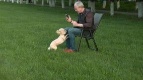 El hombre se está sentando con el teléfono y está sosteniendo un perro almacen de video