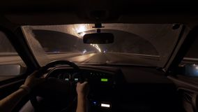 El hombre se está sentando en el asiento del coche y está montando en noche en ciudad, la visión en el panel de control y el cami almacen de video