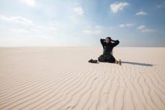 El hombre se está sentando en el medio del desierto y viste la tradición fotografía de archivo libre de regalías