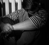 El hombre se está sentando en el piso, en la depresión, con su cabeza abajo Imagen de archivo