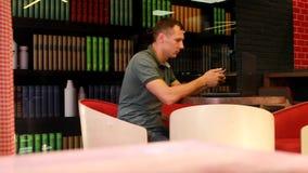 El hombre se está sentando en el escritorio con el teléfono y el ordenador portátil almacen de metraje de vídeo
