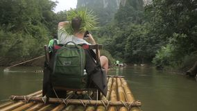 El hombre se está sentando en la silla mientras que corre en flotador-tablero rio abajo metrajes