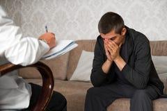 el hombre se está sentando en el sofá y las cubiertas hacen frente con las manos en la oficina del psicólogo foto de archivo