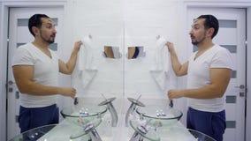 El hombre se lava para arriba delante del espejo Individuo sin afeitar cansado en una camiseta blanca almacen de video