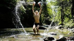 El hombre se levanta y salpica en el río de la montaña en el verano, el individuo se coloca en el agua y disfruta como un niño almacen de metraje de vídeo