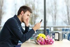 El hombre se levantaba en una fecha que comprobaba mensajes de teléfono Fotografía de archivo libre de regalías