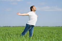 El hombre se mueve en un campo verde de la hierba Foto de archivo libre de regalías