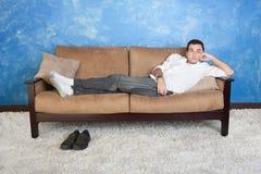 El hombre se relaja en el sofá Fotografía de archivo
