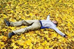 El hombre se relaja en la tierra entre las hojas amarillas de la caída en bosque Foto de archivo