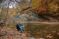 El hombre se sienta cerca de corriente de la montaña en otoño imagen de archivo libre de regalías