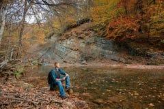 El hombre se sienta cerca de corriente de la monta?a en oto?o fotografía de archivo