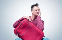 El hombre se sienta con una maleta roja que espera un viaje Concepto de la expectativa foto de archivo