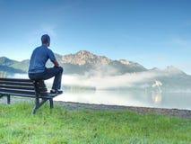 El hombre se sienta en banco de madera en la costa de las montañas del azul del bramido del lago Fotografía de archivo libre de regalías