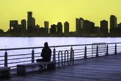 El hombre se sienta en banco de parque que mira la puesta del sol sobre Hudson River en New York City Fotos de archivo
