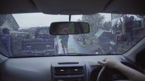 El hombre se sienta en coche lateral de la rueda derecha, da vuelta al vaso de radio, espera la conducción metrajes