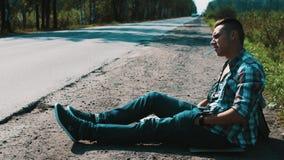 El hombre se sienta en el camino en campo con la ciudad de la muestra de la placa de la cartulina hitchhiking Dom metrajes