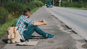 El hombre se sienta en el camino en campo hitchhiking Ayuda que espera Sostenga la hierba en boca almacen de metraje de vídeo