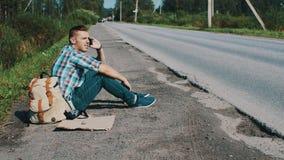 El hombre se sienta en el camino en campo hitchhiking Para ayuda que espera Coja el teléfono almacen de metraje de vídeo