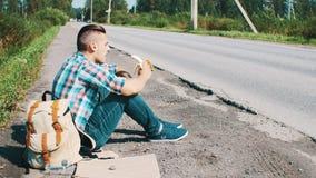 El hombre se sienta en el camino en campo hitchhiking Para ayuda que espera Consumición del plátano almacen de video