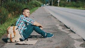 El hombre se sienta en el camino en campo hitchhiking Para ayuda que espera Hierba en boca almacen de video