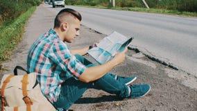 El hombre se sienta en el camino en campo hitchhiking Para ayuda que espera Mirada en mapa metrajes
