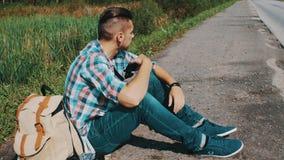 El hombre se sienta en el camino en campo hitchhiking Para ayuda que espera Ponga las gafas de sol almacen de metraje de vídeo