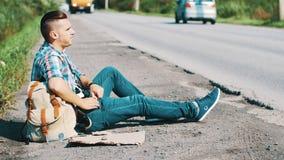 El hombre se sienta en el camino en campo hitchhiking Para ayuda que espera Smartphone de la toma metrajes