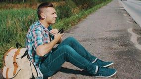 El hombre se sienta en el camino en campo hitchhiking Para ayuda que espera Suspenda las gafas de sol metrajes