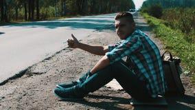 El hombre se sienta en el camino en campo hitchhiking Pulgar para arriba Cigarrillo que fuma metrajes