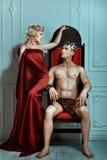 El hombre se sienta en el trono y mira a la reina Fotografía de archivo
