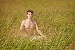 El hombre se sienta en hierba en actitud del loto Imagenes de archivo