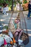 El hombre se sienta en jaula de pájaros de madera y hace la promoción Foto de archivo