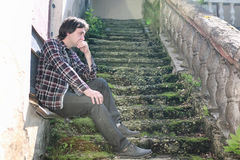 El hombre se sienta en la escalera abandonada Fotografía de archivo